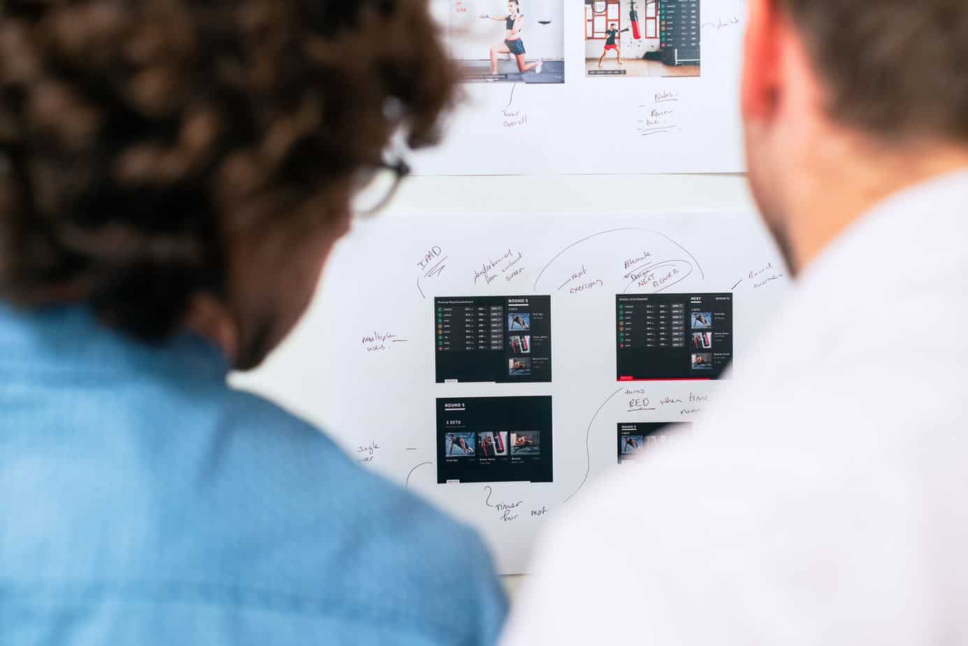 Two designers looking at whiteboard with design mockups.