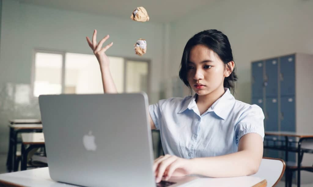Woman learning online in front of a laptop, throwing away crumbled paper notes behind.